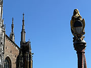 The smaller spires of Ulm minster with the shields of the fountain in the central square.